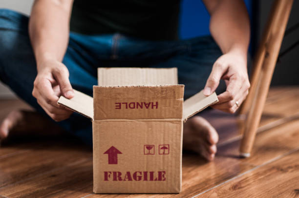A midsection front view of a young adult male Southeast Asian is unboxing a small cardboard box indoor